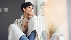 A young woman sits wrapped in a blanket looking out the window. / Une jeune femme, assise avec une couverture, regardant par la fenêtre.