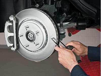 A certified Acura mechanic is inspecting the wear on the rotors. // Un mécanicien certifié Acura inspecte l'usure des disques