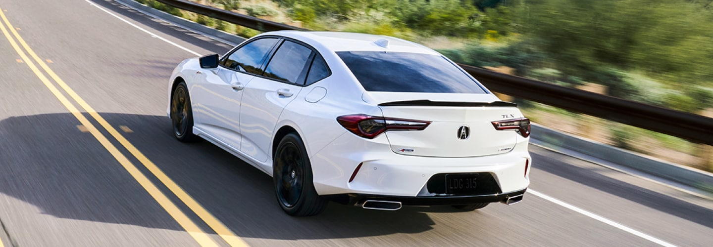 A white Acura TLX cruising around on the highway at a high speed. / Une Acura TLX blanche roulant sur l'autoroute à grande vitesse