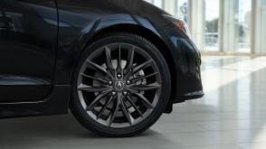 Tire profile shot of the front right rim and tire of an Acura ILX parked in a vehicle showroom. // Plan de profil de la jante avant droite et du pneu d'une Acura ILX stationnée dans une salle d'exposition de véhicules