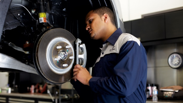 A certified Acura technician is inspecting the rotors and brake pads of an Acura vehicle.// Un technicien Acura certifié inspecte les disques et les plaquettes de frein d'un véhicule Acura.