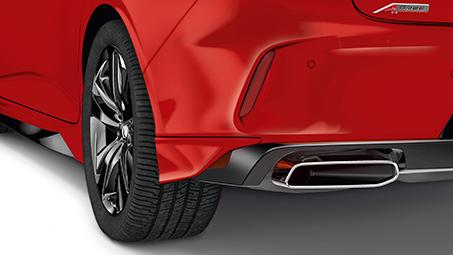 Close-up rear-view of a red Acura, with back left wheel and bumper in view.  // Vue arrière rapprochée d'une Acura rouge, avec la roue arrière gauche et le pare-chocs en vue.