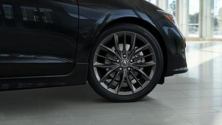 Low, angled shot of the front side of a black Acura parked inside a showroom during the day. // Plan bas et incliné de l'avant d'une Acura noire garée dans une salle d'exposition pendant la journée.