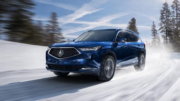 An MDX driving through the hills during the winter over a road that is covered in snow. // Un MDX roulant à travers les collines pendant l'hiver sur une route couverte de neige.