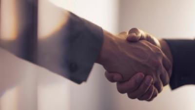 Two people shaking hands in agreement. // Deux personnes se serrant la main en accord.