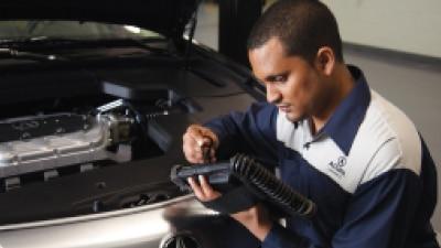 An Acura certified technician is reviewing the diagnostics of the vehicle on a portable tablet. // Un technicien certifié Acura examine les diagnostics du véhicule sur une tablette portable.