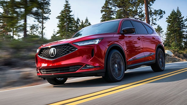 Side-angle, front end view of a steel metallic, all-new 2022 Acura MDX driving through a desert.
