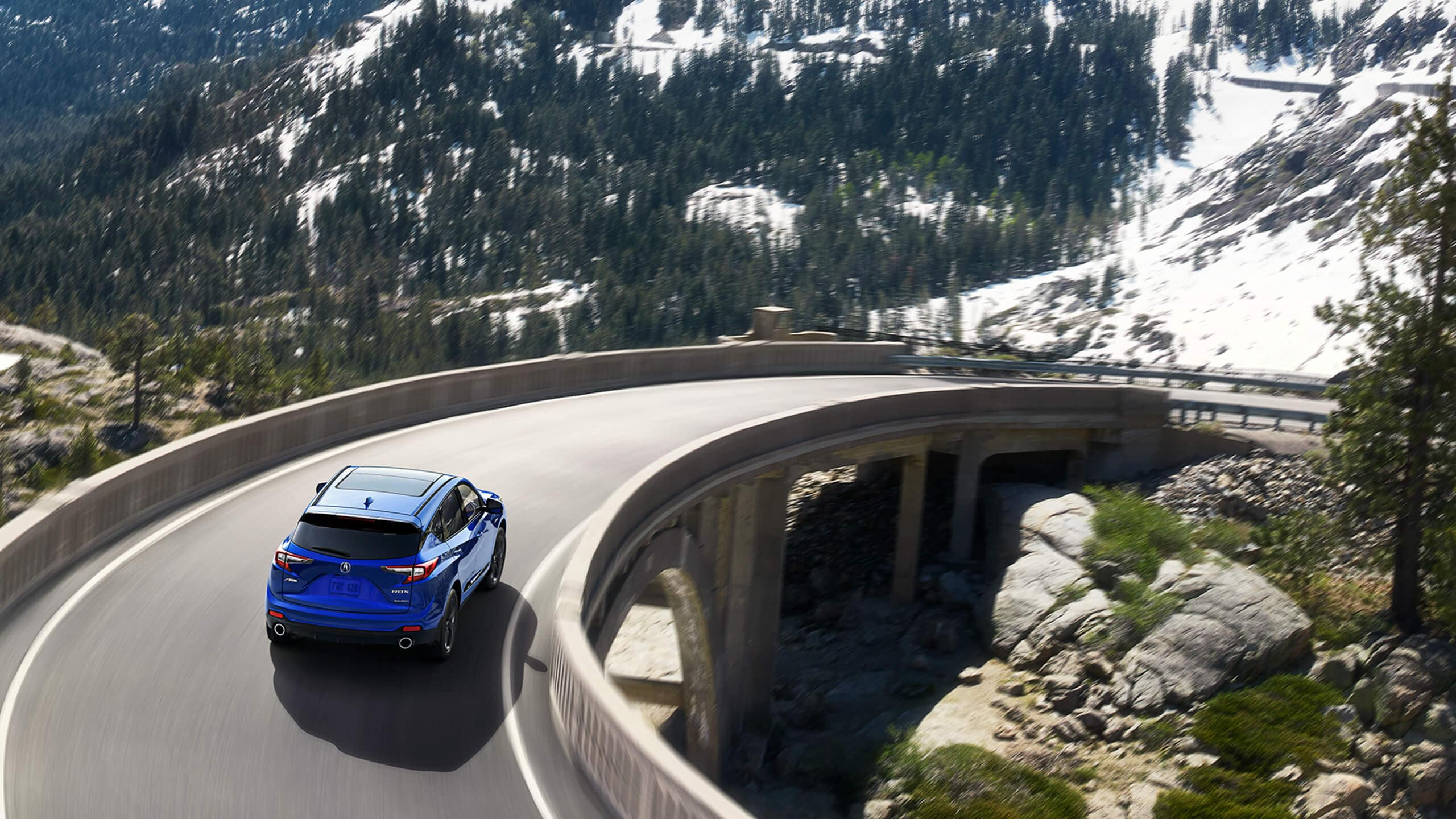 Blue 2020 Acura RDX driving down a scenic, curved road X