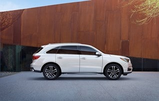 Image of side profile of white 2017 Acura MDX in front of hardwood backdrop