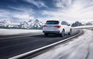 Image of rear white 2017 Acura MDX driving on snowy road