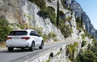 Image of rear white 2017 Acura MDX driving outdoors